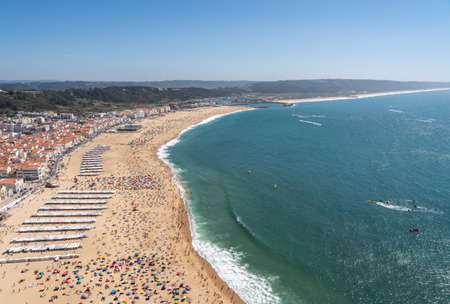 Crowded beach of Nazare from above with tourists relaxing on the sand