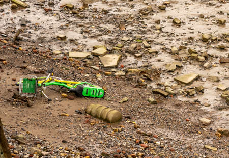 Woolwich, UK - 5 October 2019: Lime e-scooter dumped into the river in East London