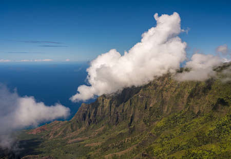 Fluted rocks of the Na Pali mountains with clouds forming over the peaks from Kalalau lookout on Kauai