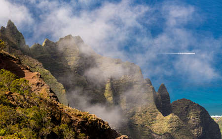 Fluted rocks of the Na Pali mountains through the clouds from Kalalau lookout on Kauai