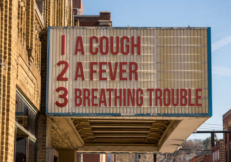 Cinema billboard with three main symptoms or signs of a coronavirus or Covid-19 infection of coughing, feverish and trouble with breathing Standard-Bild