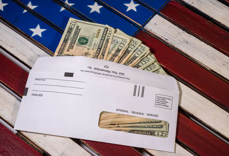 Stack of 20 dollar bills in IRS envelope to illustrate coronavirus stimulus payment or estimated tax payments
