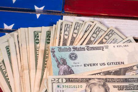Stack of 20 dollar bills with illustrative coronavirus stimulus payment check on USA flag 스톡 콘텐츠 - 144499193