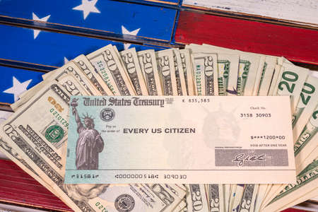 Stack of 20 dollar bills with illustrative coronavirus stimulus payment check on USA flag