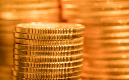 Focus on a stack of gold coins with other coin stacked in the background out of focus Banque d'images