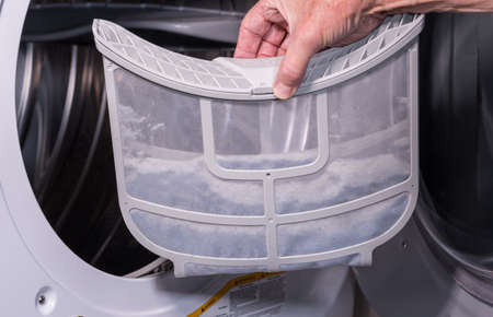 Senior caucasian man holding the lint filled trap from a front loading tumble dryer Reklamní fotografie