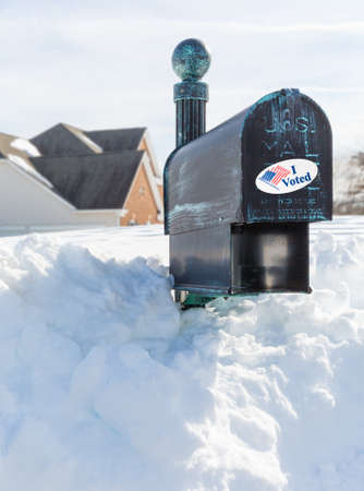 Metal mailbox for rural homes buried in deep snow with I Voted sticker as concept for voting by mail or absentee ballot paper