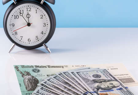 Stack of 100 dollar bills with illustrative coronavirus stimulus payment check and alarm clock to show delay in receiving money