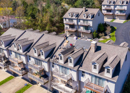 Morgantown, WV - 22 April 2020: Aerial view of roofing contractors replacing the old shingles on a townhouse roof