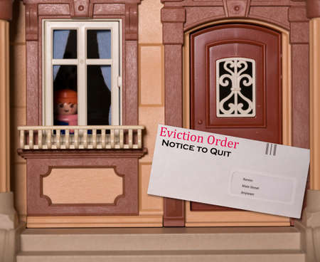 Envelope being served at toy dollhouse containing an eviction notice due to failure to pay rent on the property 免版税图像