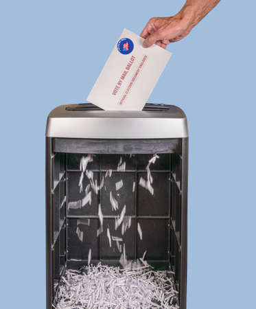 Vote by mail or absentee ballot being shredded in office paper shredder as illustration of voting fraud or lost votes in Presidential election