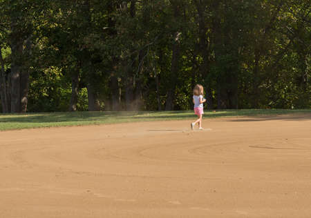 Small toddler girl playing in the sand and dirt of an empty baseball field in the infield area