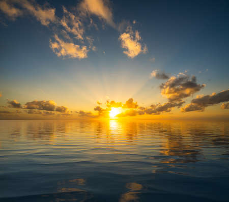 Dramatic sunrise or sunset reflected into the calm waters of an artificial ocean to represent peace or heaven