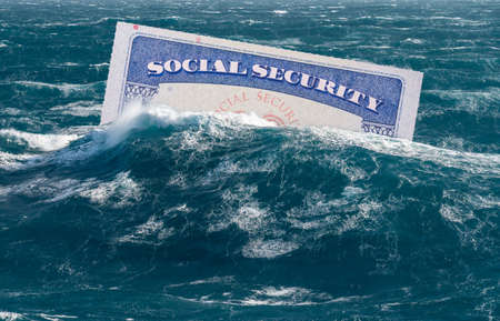 Social Security card sinking underwater in stormy seas as concept for issues around funding of USA pensions to seniors