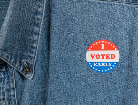 I Voted Early sticker or campaign button on the blue denim working shirt collar for elections in the USA