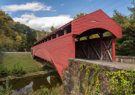 Well maintained Burr Truss covered bridge in Barrackville West Virginia crossing stream in the fall 写真素材