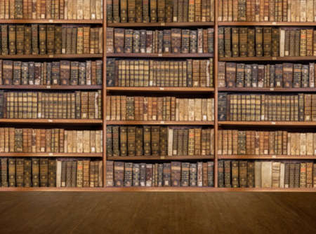 Defocused and blurred image of old antique library books on shelves with wooden floor for use in video conferencing background