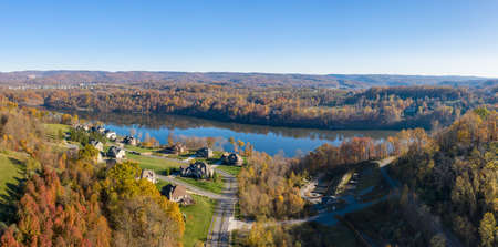Aerial drone panorama of single family houses by Cheat Lake near Morgantown in autumn