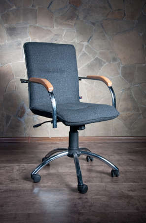 Office chair with armrests on a stone background photo