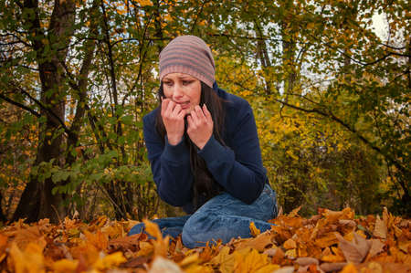 crying girl on the fallen leaves