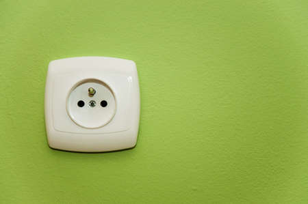 alternating current: white socket on a green wall