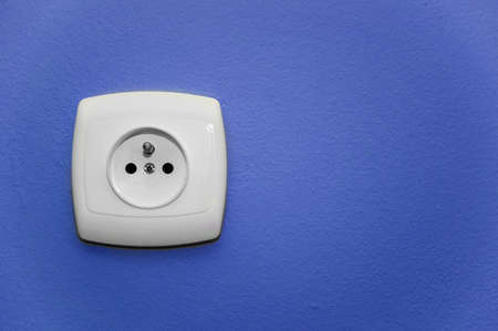 alternating current: white socket on a blue wall