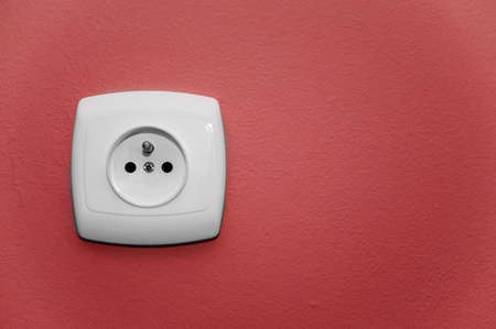 alternating current: white socket on a red wall Stock Photo