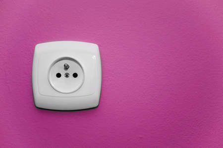 alternating current: white socket on a pink wall