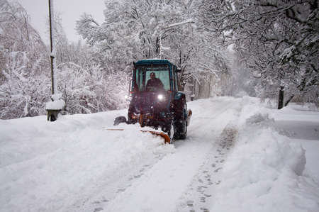 Tractor cleans snow on the road photo