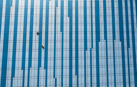 two people wash skyscraper windows photo