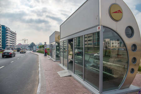 conditioned: DUBAI, UAE - MARCH 4: An air conditioned bus stop in Dubai with a tourist reflection in the glass. All of the bus stops here are air-conditioned on March 4, 2014 in Dubai, UAE.