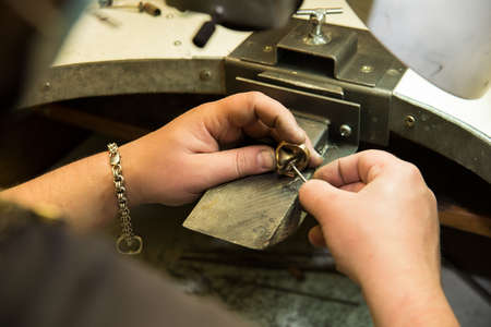 Goldsmith polishing gold ring with  hands photo