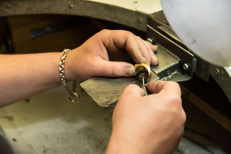Goldsmith polishing gold ring with  hands