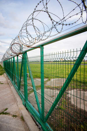 barbed wire fence: green fence with barbed wire Stock Photo