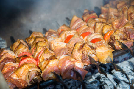 spit: meat with vegetables roast on the coals Stock Photo