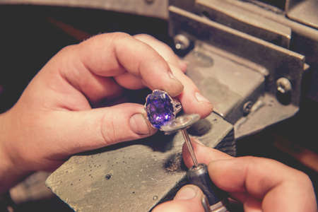 Le maître joaillier produit une bague en or avec une grosse pierre bleue