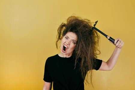 genervtes Mädchen kämmt sich mit einem Rechen die Haare Standard-Bild