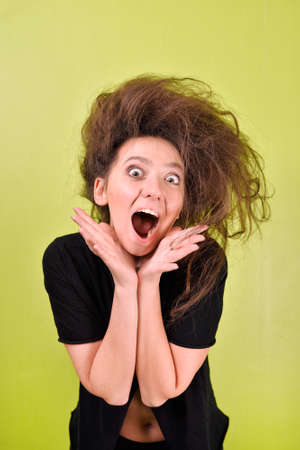 girl with an open mouth and a strange hair style on a yellow background 스톡 콘텐츠