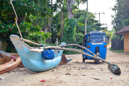 Fishing boat and tut-tuk near the shore in Sri Lanka Stock Photo