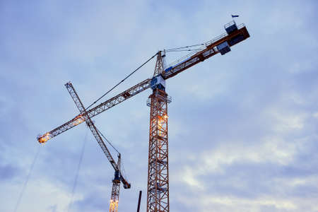 Construction cranes against the dark sky background Stock Photo