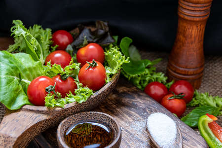tomatoes and green leaves for salad next to olive oil and salt on table