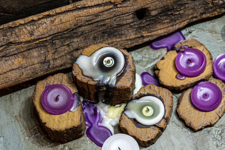dull aromatic candles melted in rustic wood in low light