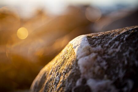 Stony beach stones and rocks sunlit in the evening closeup, texture sunset and sunrise