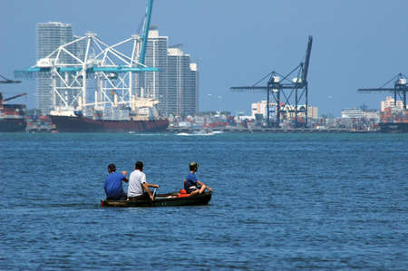 seaport: Miami seaport with a small rowing boat and 3 people in the foreground
