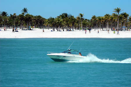 Fun in the boat - motorboat speeding by the beach