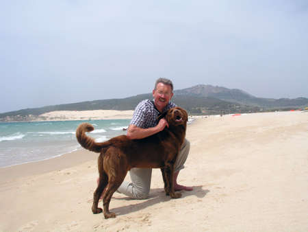 mans best friend: Mans best friend - middle aged man on the beach with his dog Stock Photo