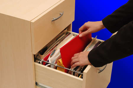 Filing Cabinet - woman putting back an important file into cabinet photo
