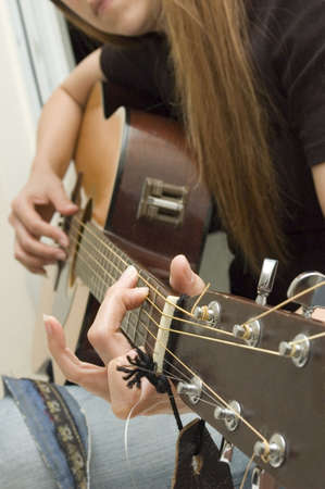 Young woman playing guitar - shallow depth of field
