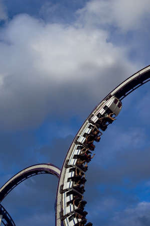 looping: Roller Coaster running into a loop with blue sky in the background