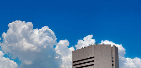 Skyscraper in front of blue sky with clouds photo